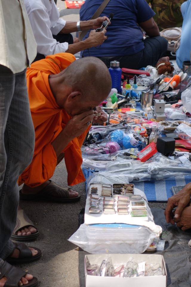 Monk with magnifying glass looking at amulet craving