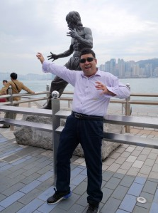 Tourists posing in front of statute of Bruce Lee on the Avenue of Stars