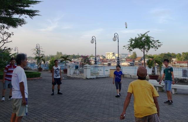 Playing a kick shuttle game on the river front