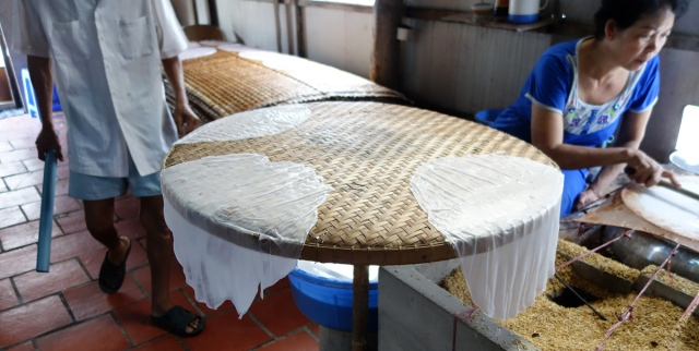 Cooling rice paper before putting on tray in back for drying