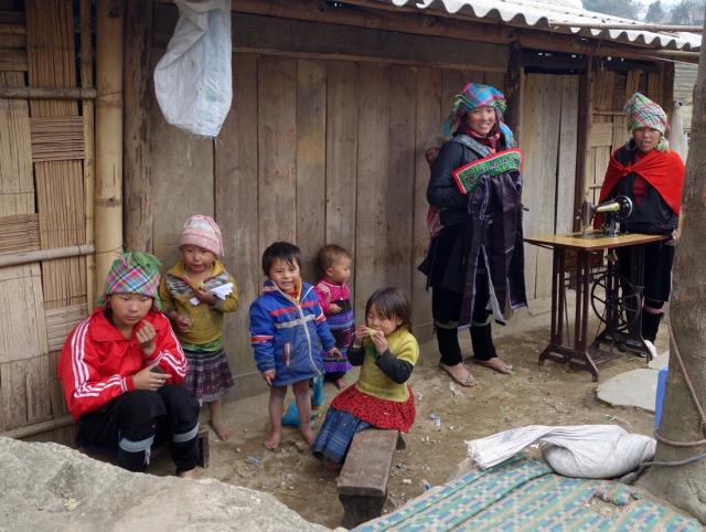 Women and children -- notice sewing machine in yard
