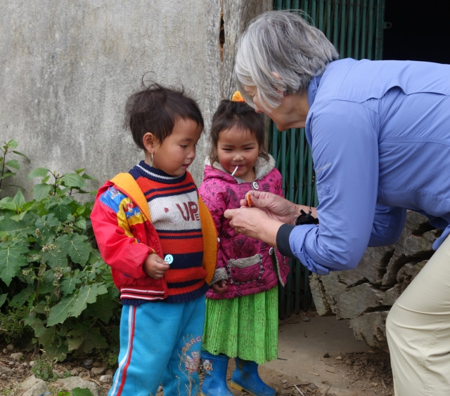 Giving some stickers to two children along the road